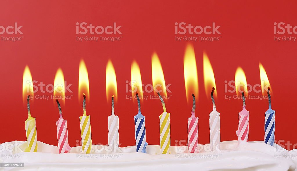 Row of ten colorful birthday candles lit on a red background stock photo