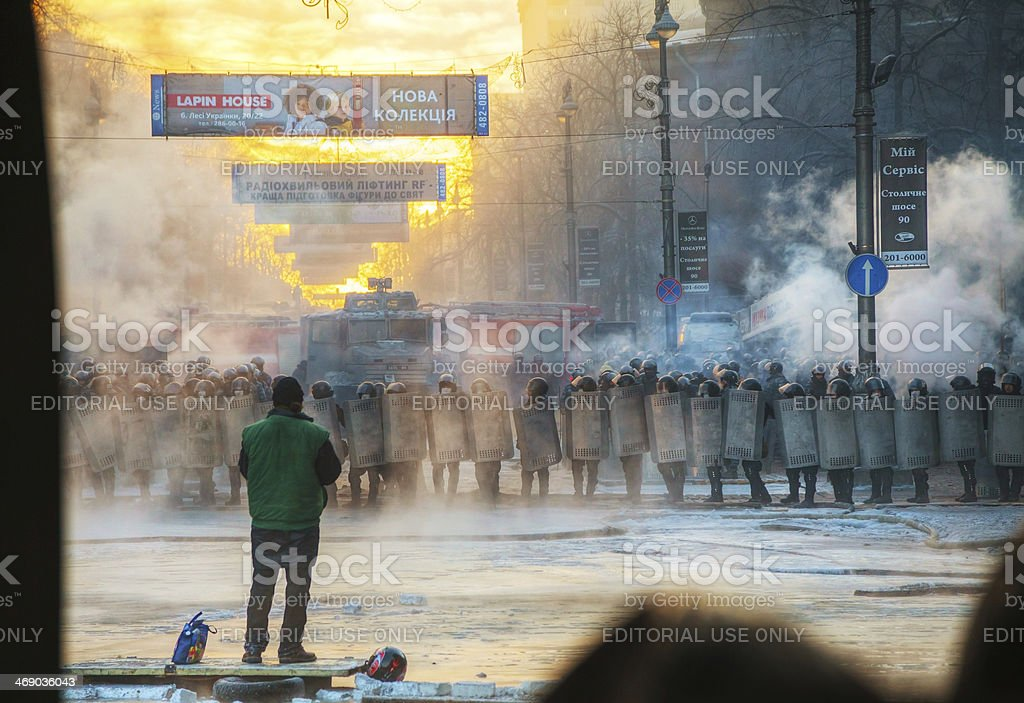 Row of the riot police with a priest stock photo