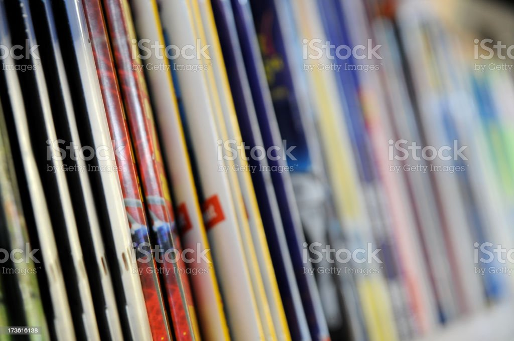 A row of thin, staple-bound magazines in a kiosk stock photo