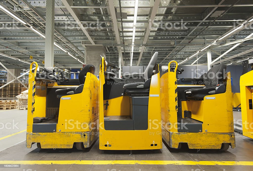 Row of three parked yellow forklift in industry warehouse royalty-free stock photo