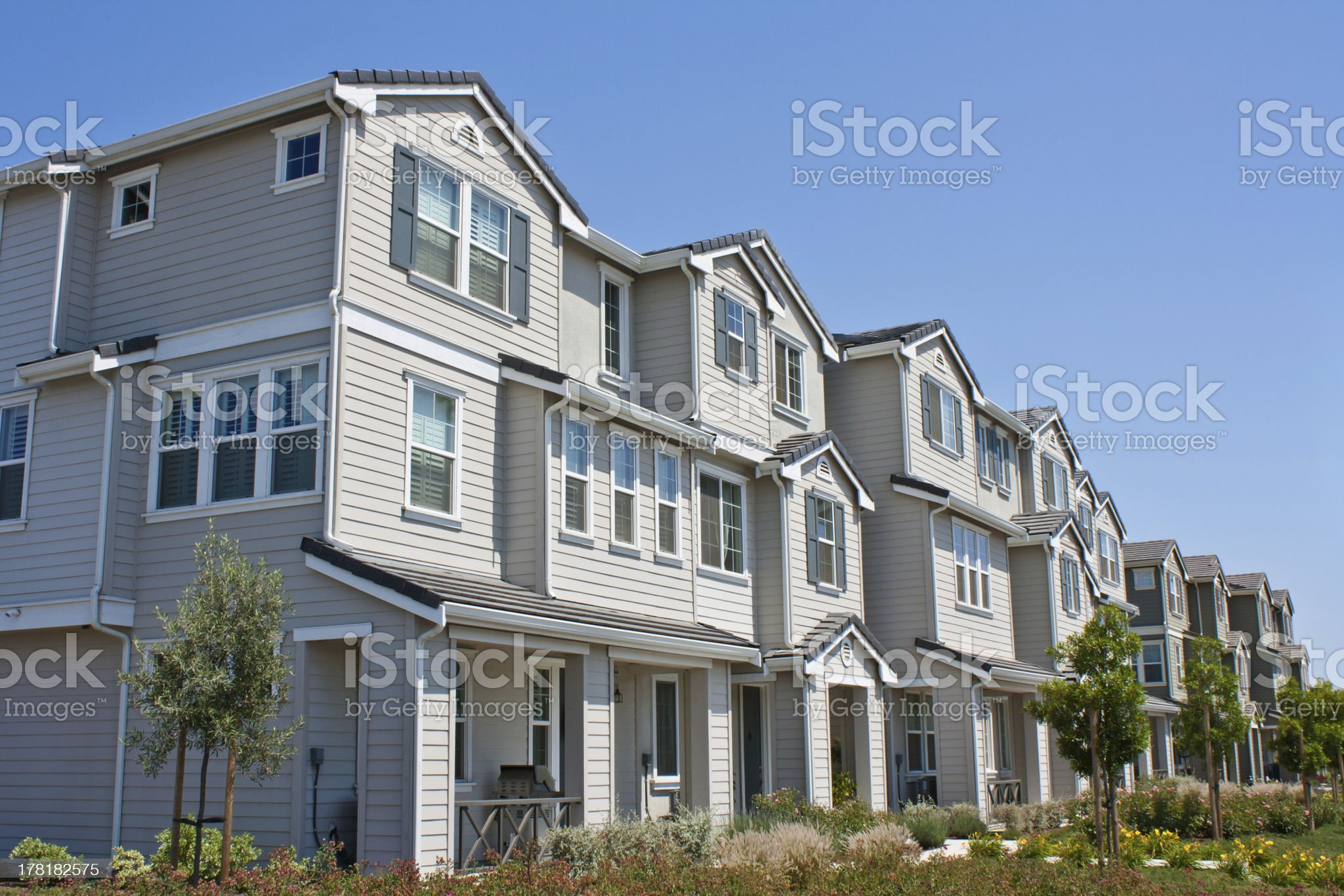 Row of three story town homes with landscaped lawns royalty-free stock photo