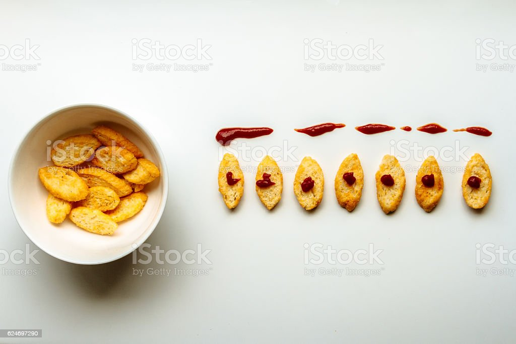 Row of toasts next to white bowl full of toast stock photo