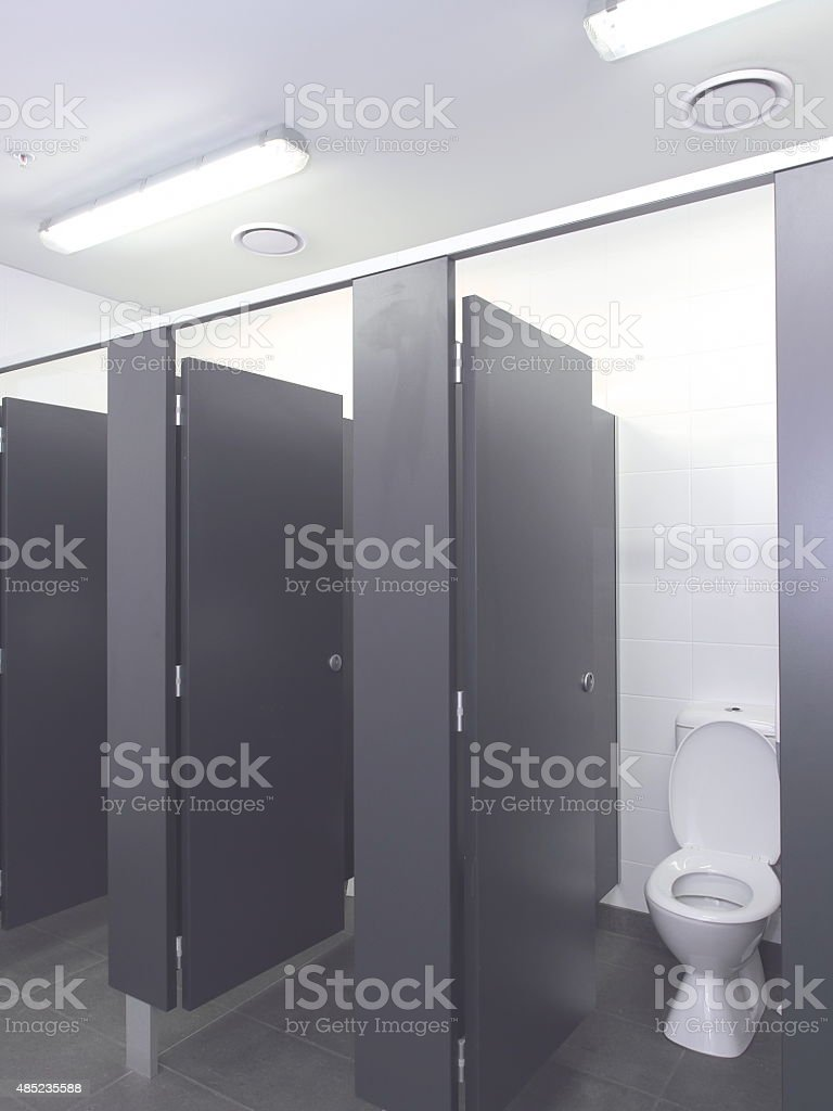 Row of toilet cubicles in a pristine industrial lavatory stock photo