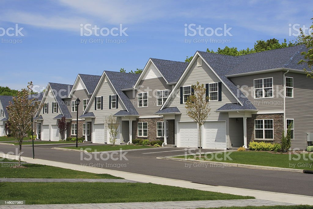 Row of townhouses with triangular roofs on residential road stock photo