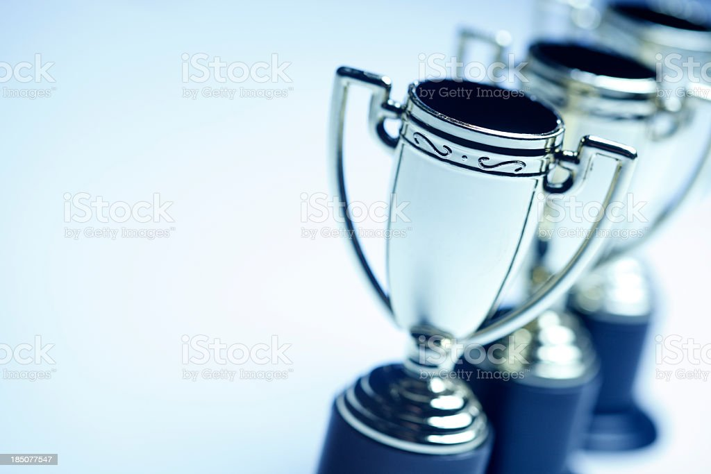Row of Trophies on blue background stock photo