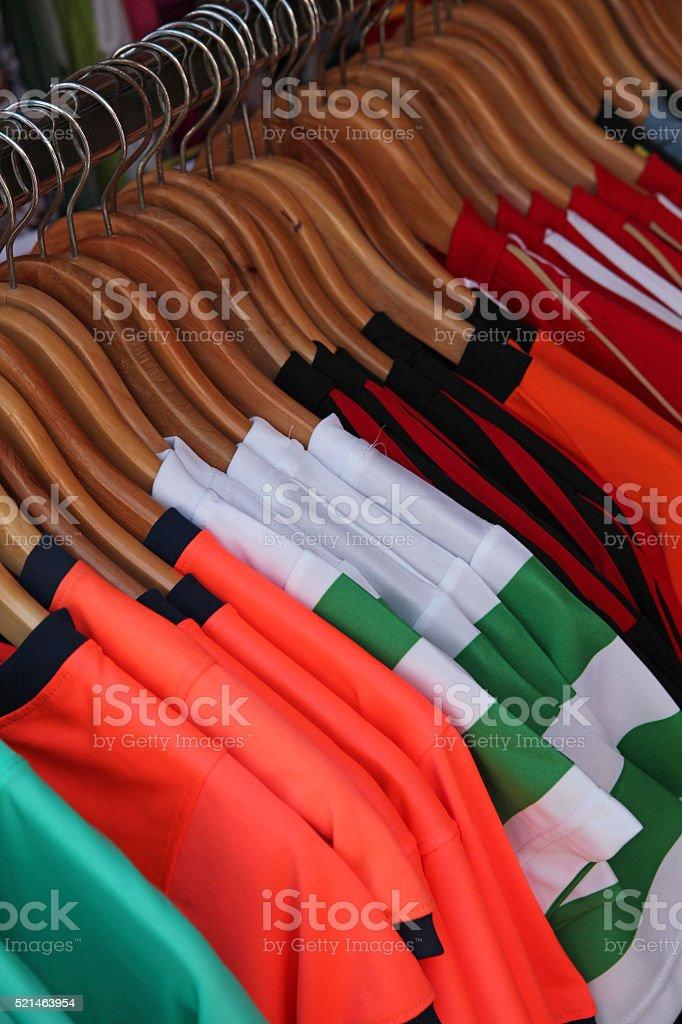 Row of Tshirts hanging on coathangers stock photo