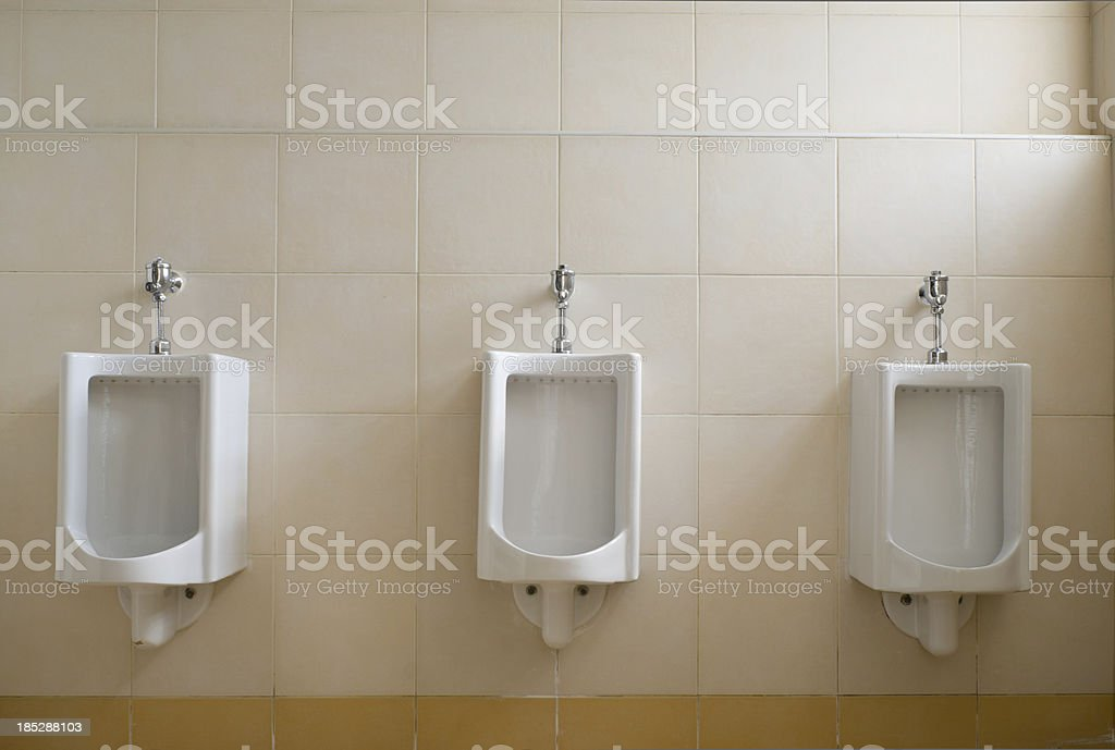 row of urinals in empty clean restroom royalty-free stock photo