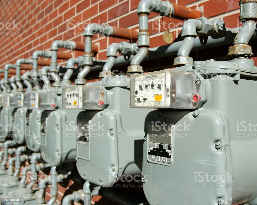 Row of water meters on brick wall royalty-free stock photo