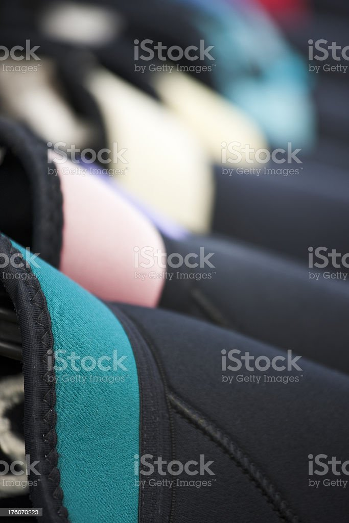 Row of Wetsuits Hang on Rack, Colorful Collars, Pattern stock photo