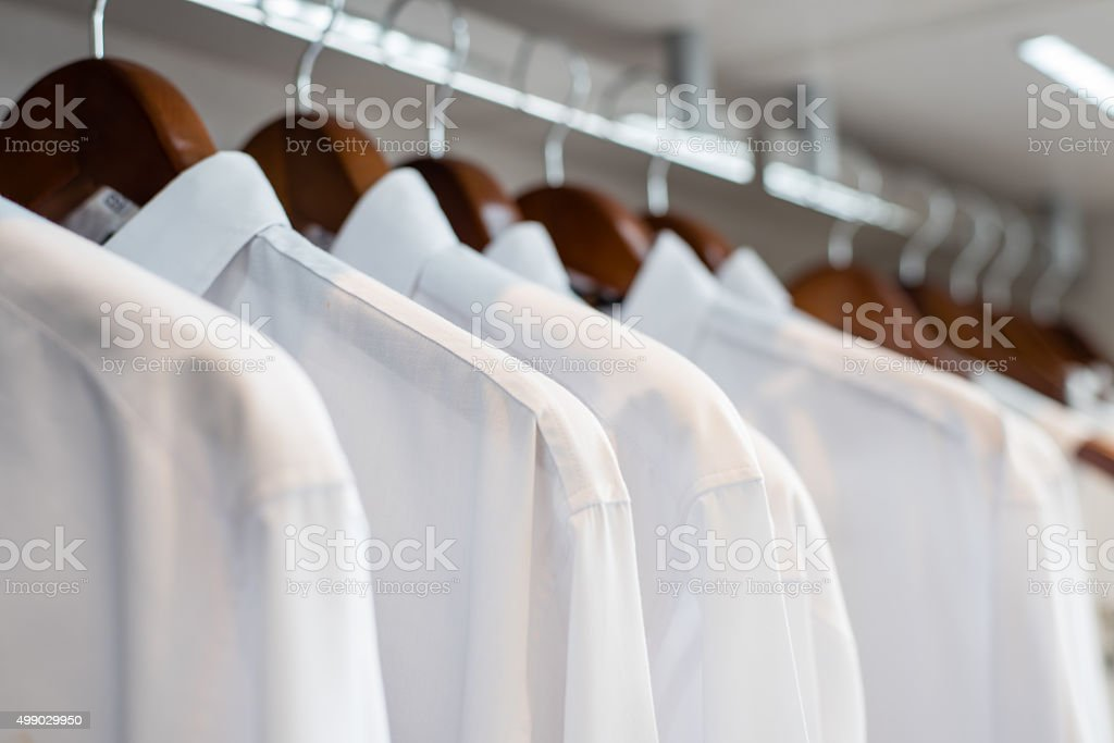 row of white shirts hanged in closet (soft focus) stock photo