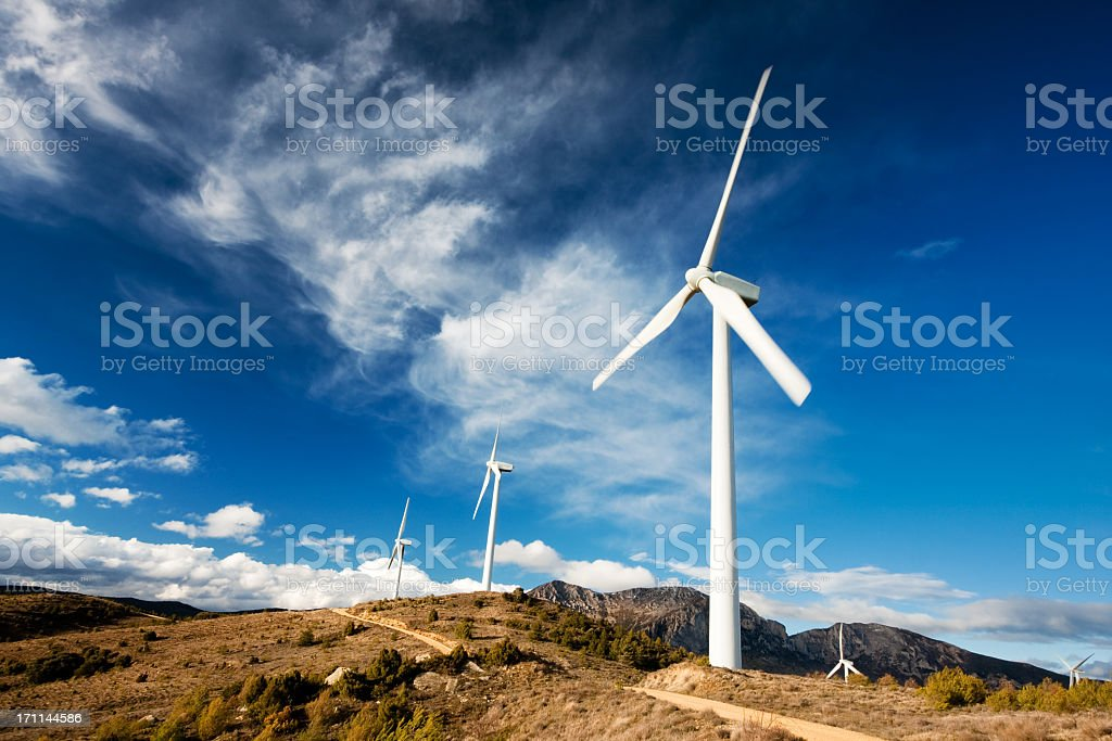 Row of white wind turbines in motion on a cloudy day royalty-free stock photo