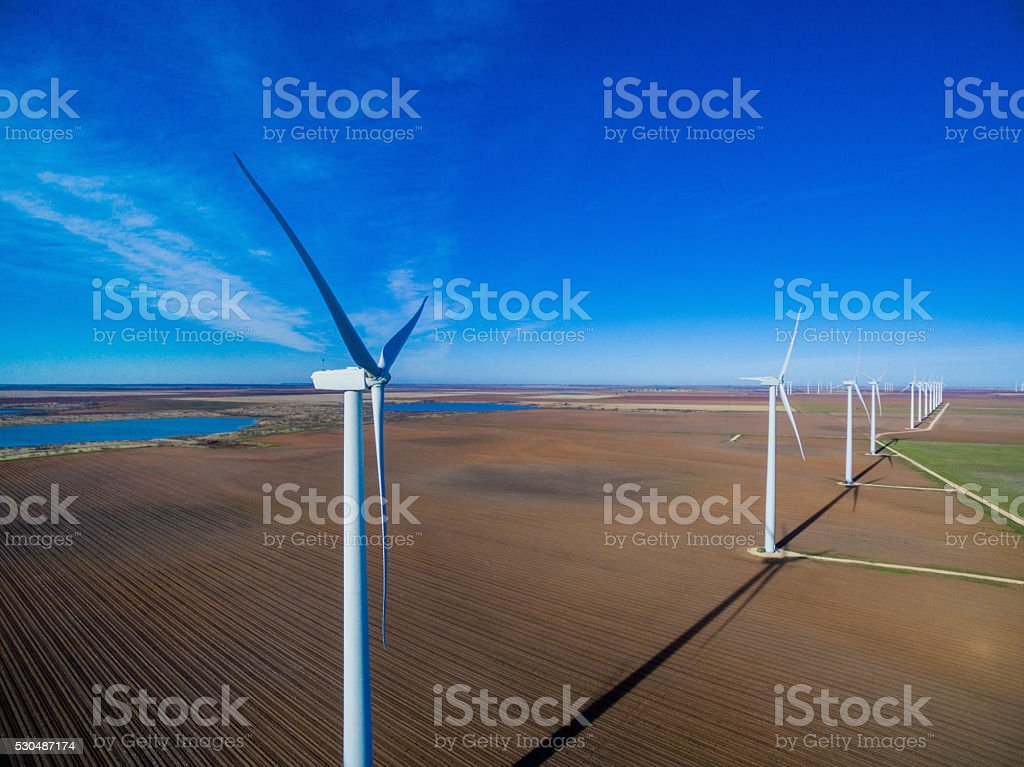 Row of wind turbines against blue sky stock photo