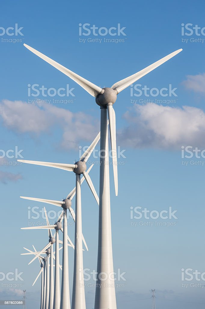 Row of wind turbines and blue sky stock photo