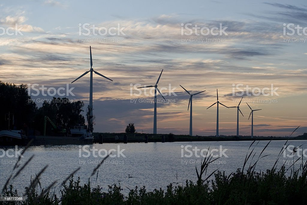 row of windmill silhouettes on waterside royalty-free stock photo