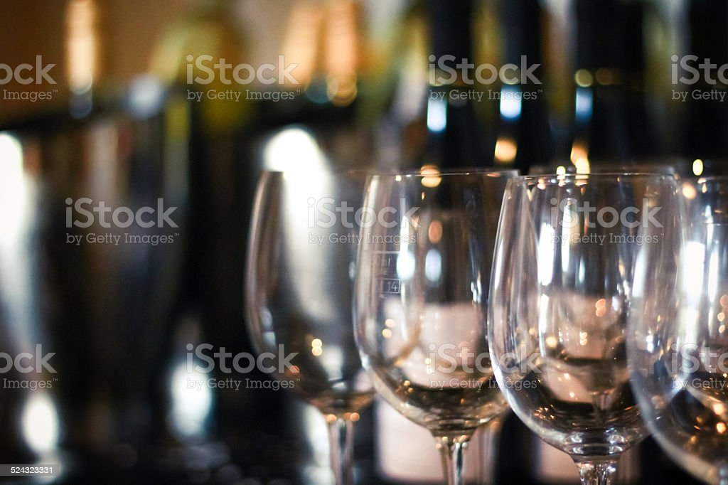 Row of wine glasses in front of wine bottles stock photo