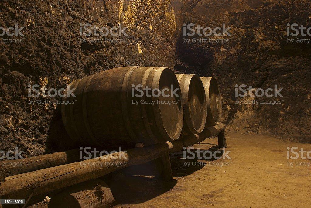 Row of wine tuns on wooden platform underground stock photo