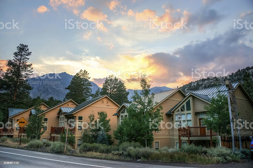 Row of wooden houses with mountains and sunset in background stock photo