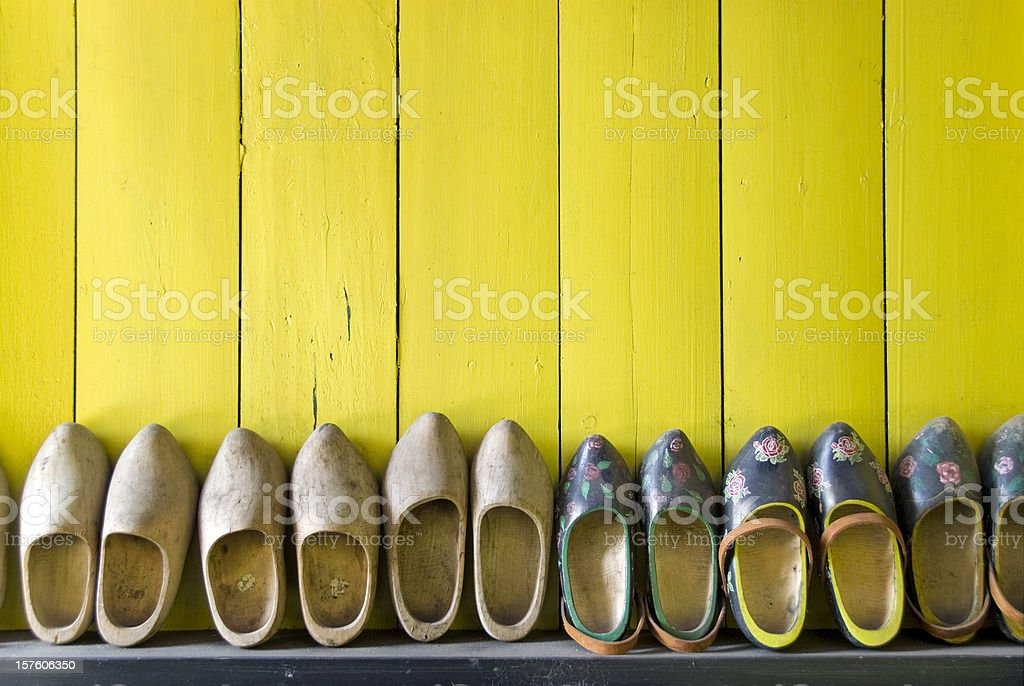 Row of wooden shoes against a yellow wall stock photo