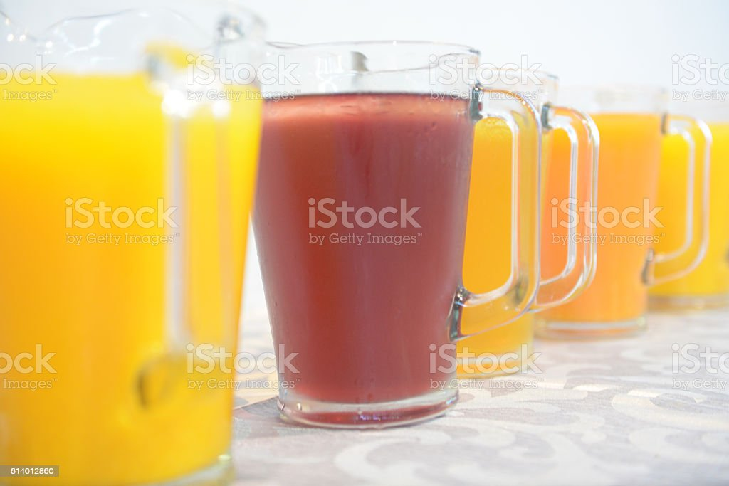 Row of  yellow and red fruit juices in jugs stock photo