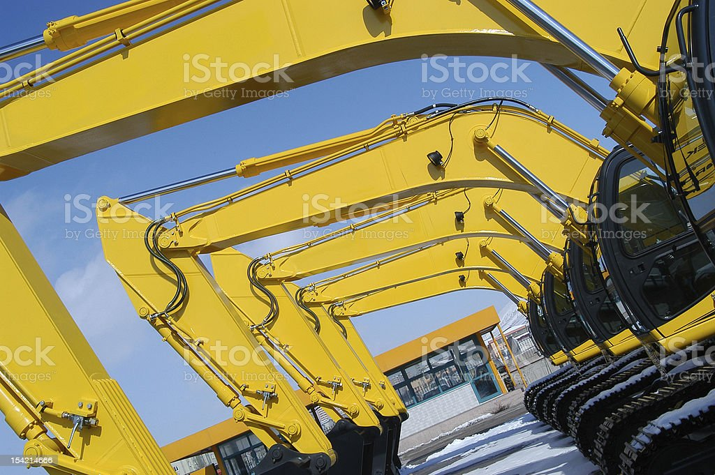 A row of yellow excavators in the yard stock photo