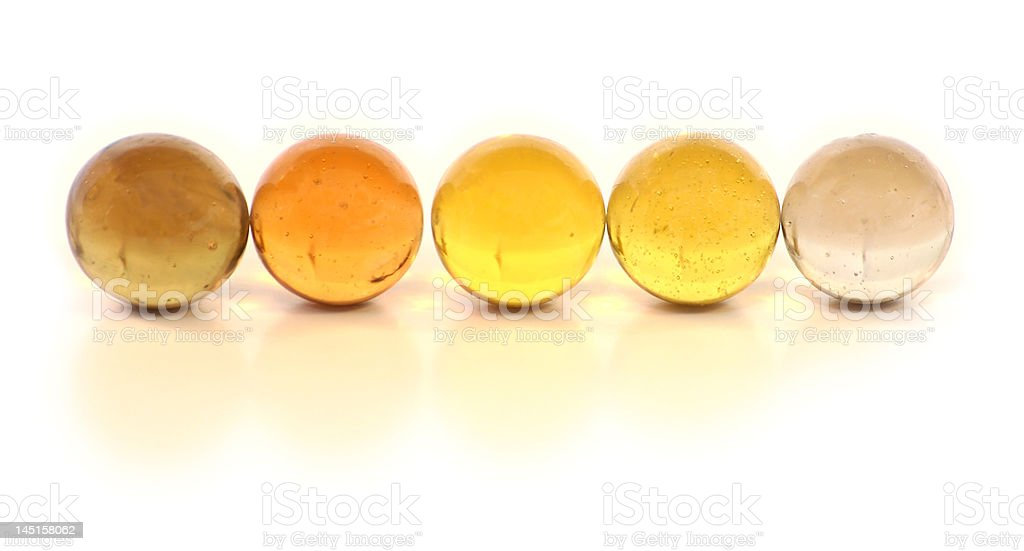 Row of yellow glass marbles fading from light to dark stock photo