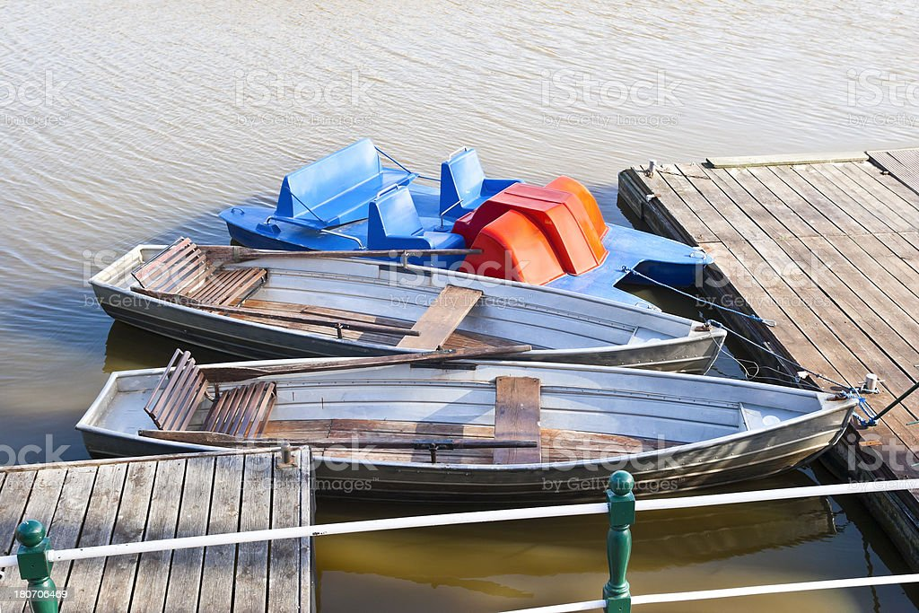 Rowboat and pedal boat at jetty royalty-free stock photo