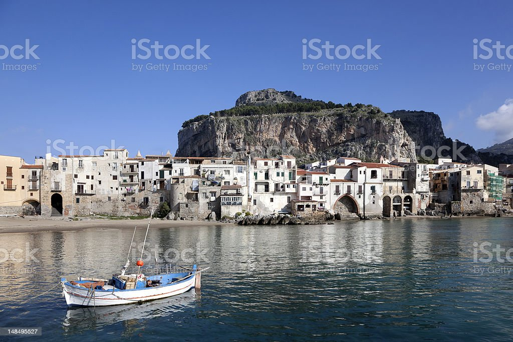 Rowboat, Old Buildings and mountain at Cefalu Beach Italy stock photo