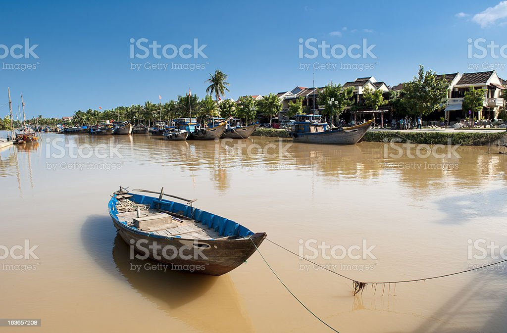 Rowboat on river with ancient town at background royalty-free stock photo