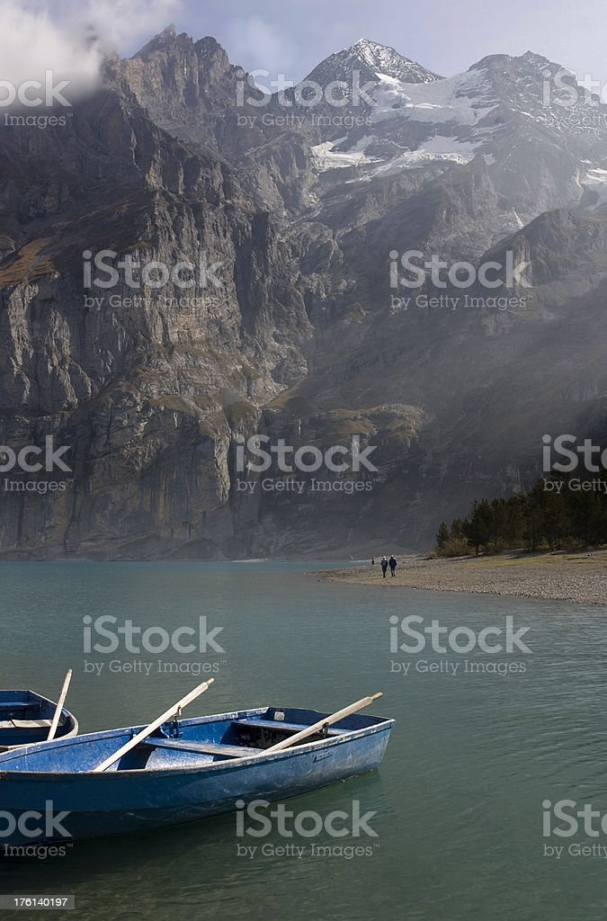 Rowboats in Swiss lake shown against sheer rock walls stock photo