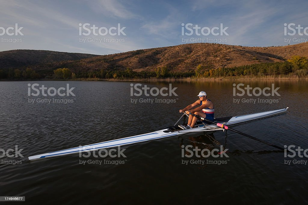Rower man sculling on lake at sunset stock photo