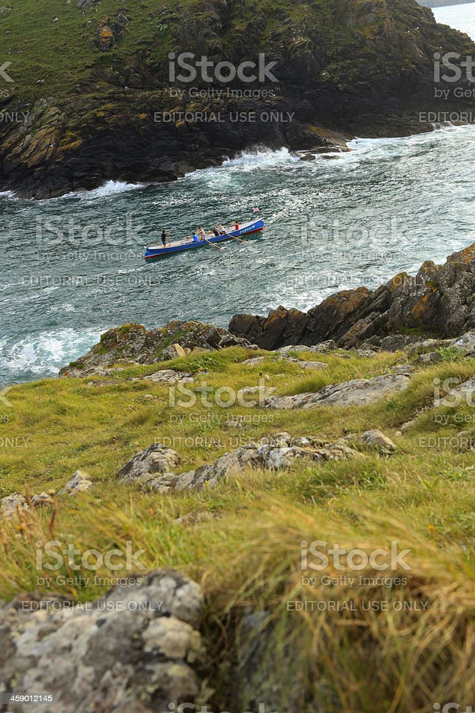 rowers exercising in a rowboat along the Cornish coast stock photo
