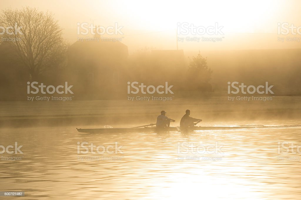 Rowers in misty morning sunrise stock photo