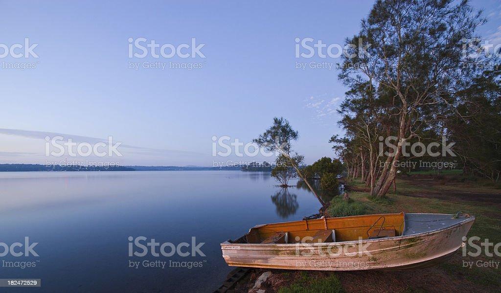Rowing boat on shore at Sunrise. Lake Macquarie NSW Australia royalty-free stock photo
