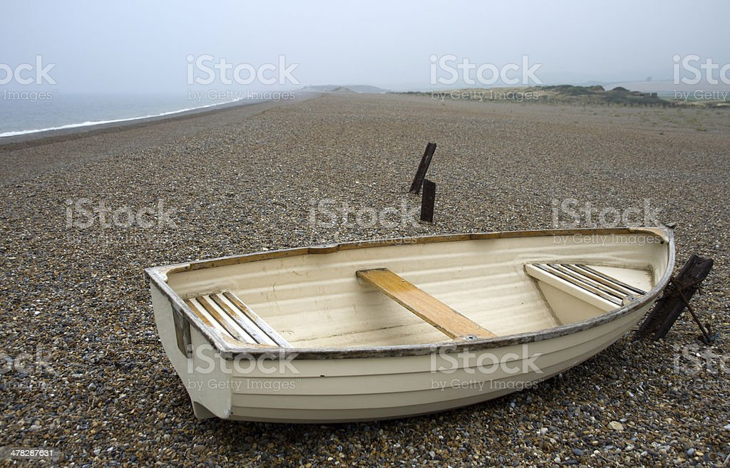 Rowing boat on stone covered beach in Norfolk royalty-free stock photo