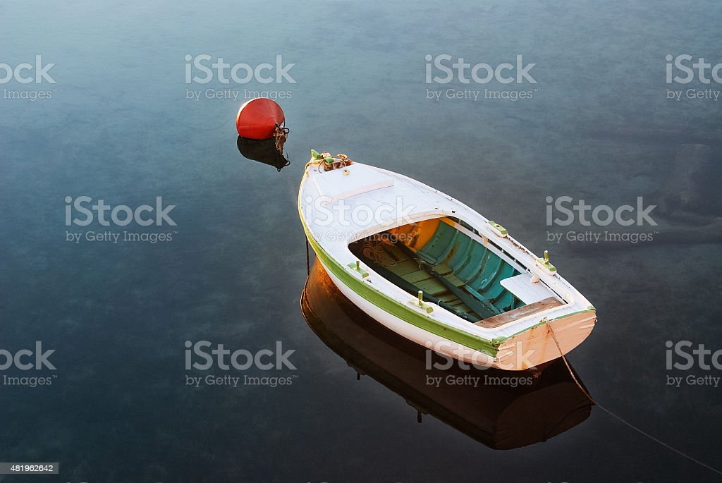 Rowing boat to the buoy in the harbor stock photo