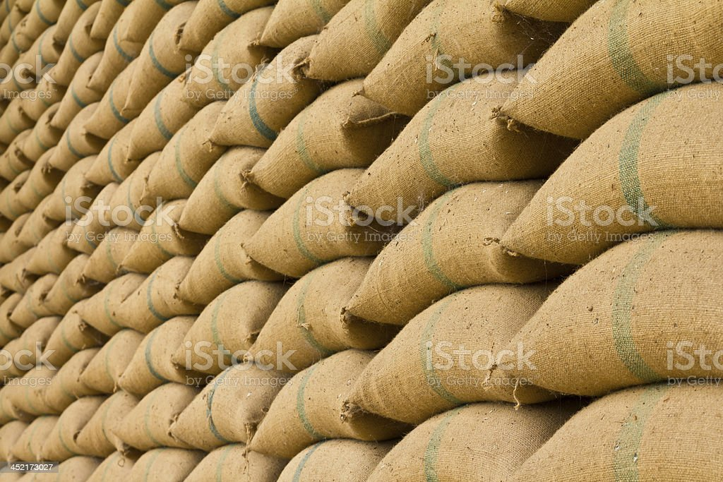 Rows and piles of yellowish old hemp sacks stock photo