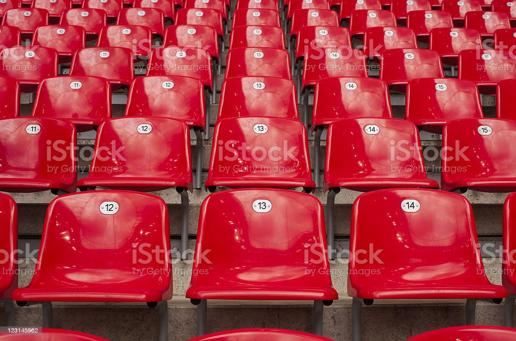 Rows and rows of red stadium seats stock photo