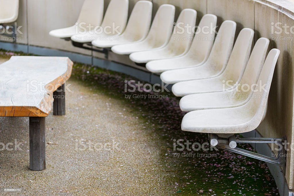 Rows of an empty white plastic seats in park. stock photo