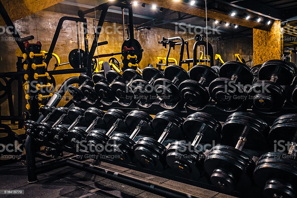 Rows of black dumbbells in gym center stock photo