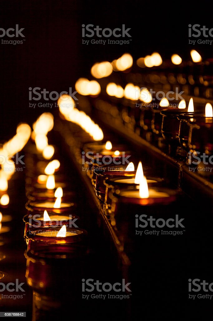 Rows of burning candles inside a curch stock photo