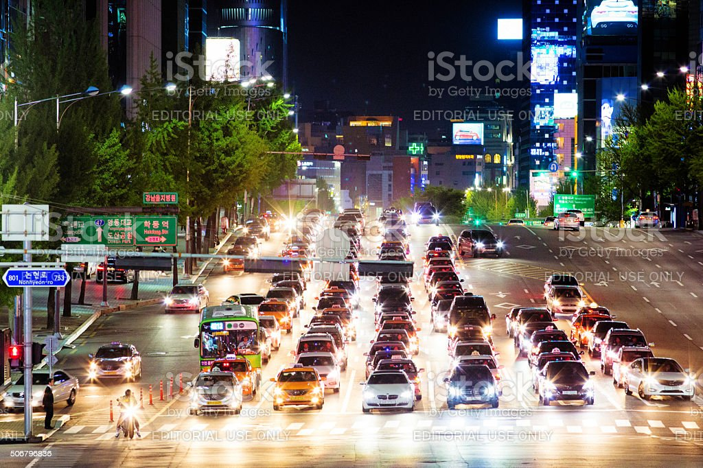 Rows of cars waiting for traffic light at night stock photo