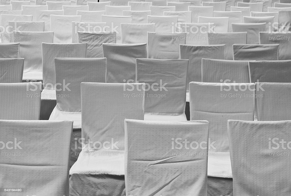 rows of chairs with white covers stock photo