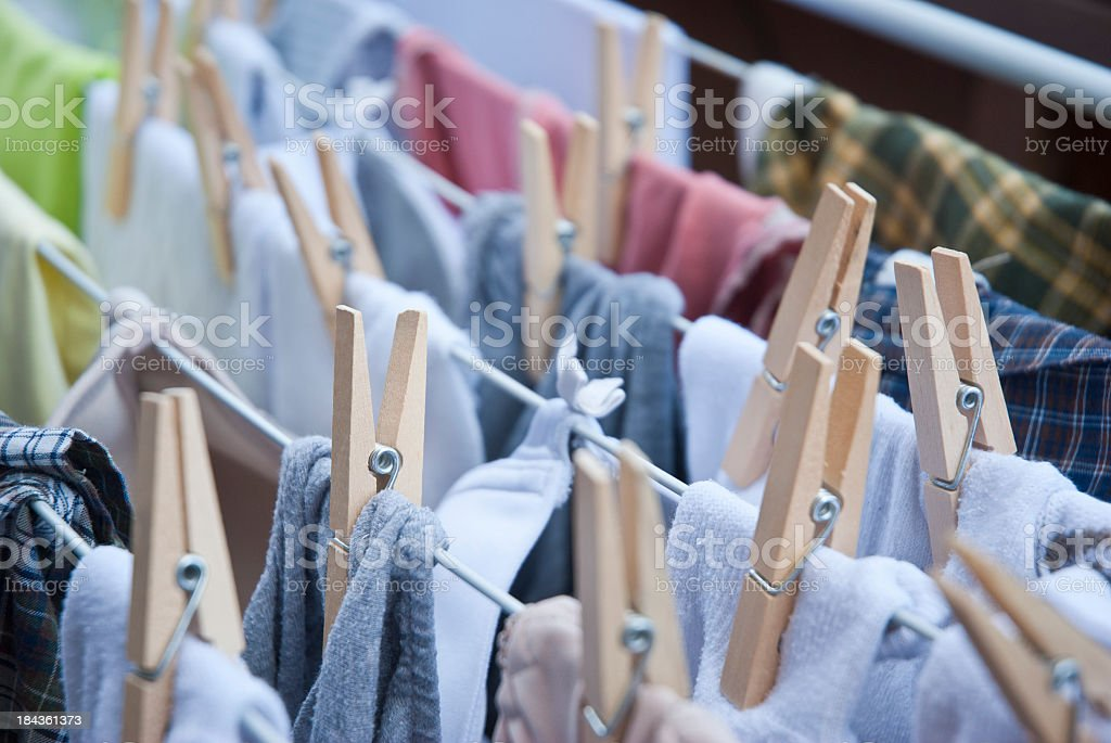 Rows of clothing hanging on a line with pegs stock photo