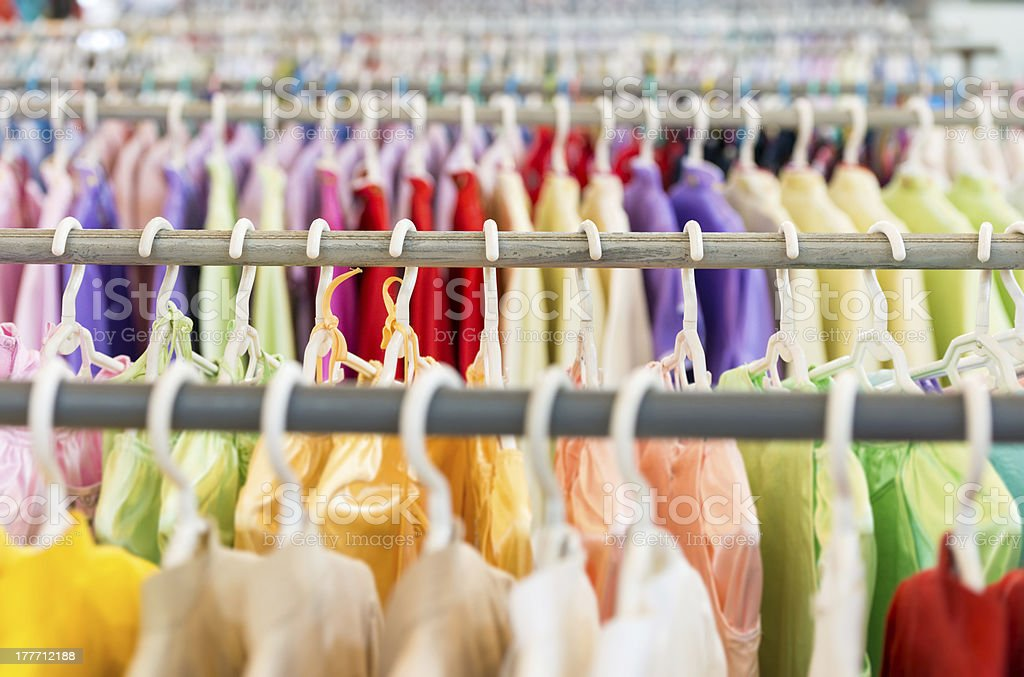 Rows of colorful clothes hanging in a shop royalty-free stock photo