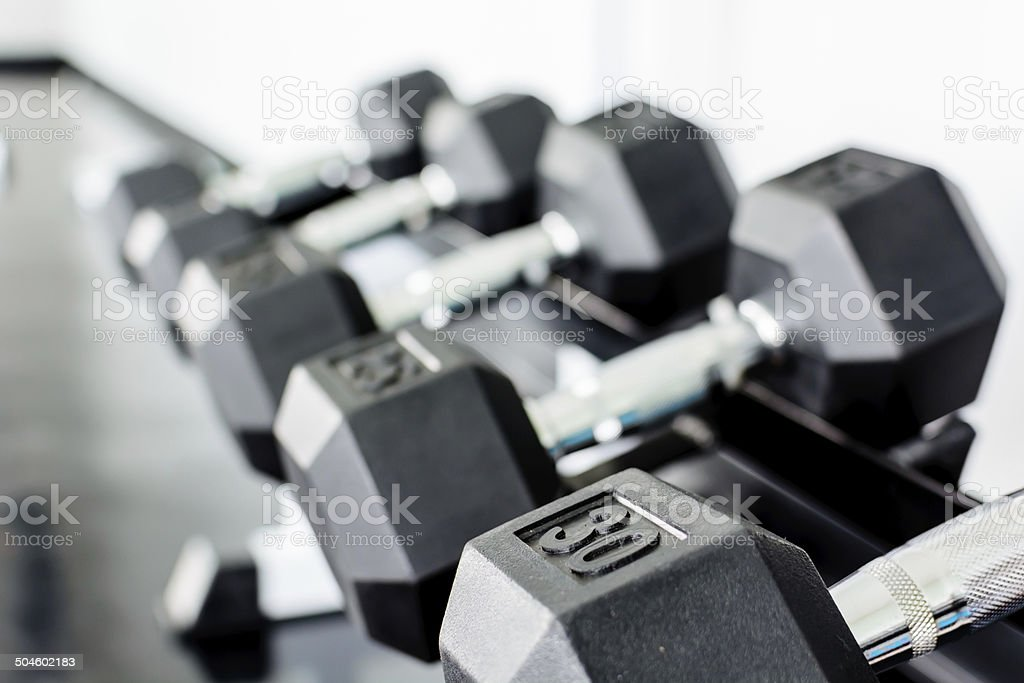 rows of dumbbells on a rack in a gym stock photo