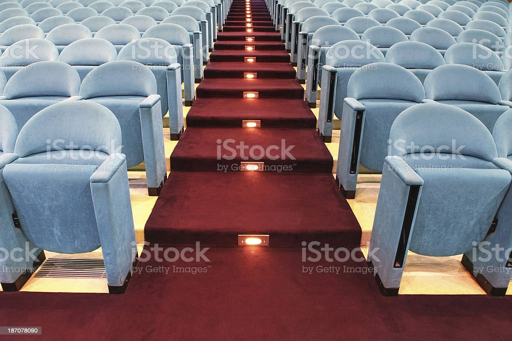 Rows of empty theater seats with red carpet royalty-free stock photo