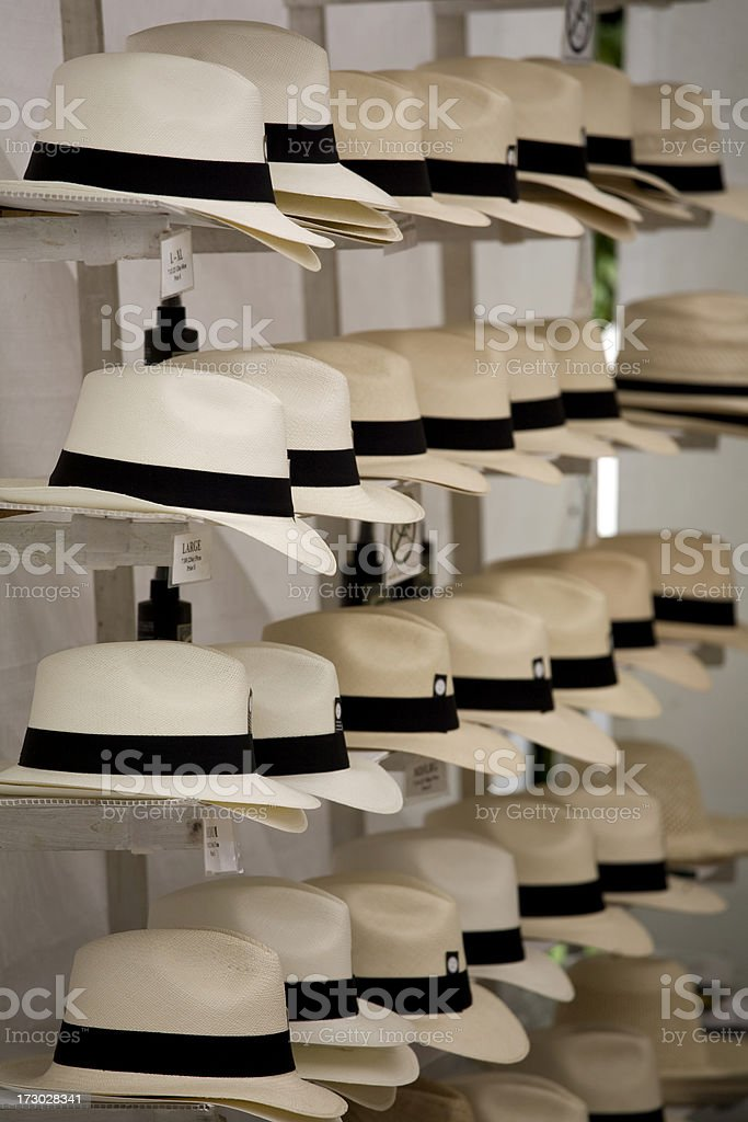 rows of identical straw hats hanging on a wall rack royalty-free stock photo