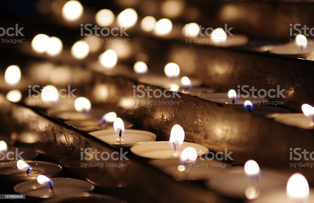 Rows of lit tea candles in sepia tones royalty-free stock photo