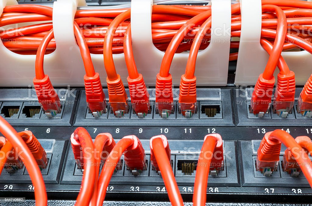 Rows of network cables connected to router and switch hub stock photo