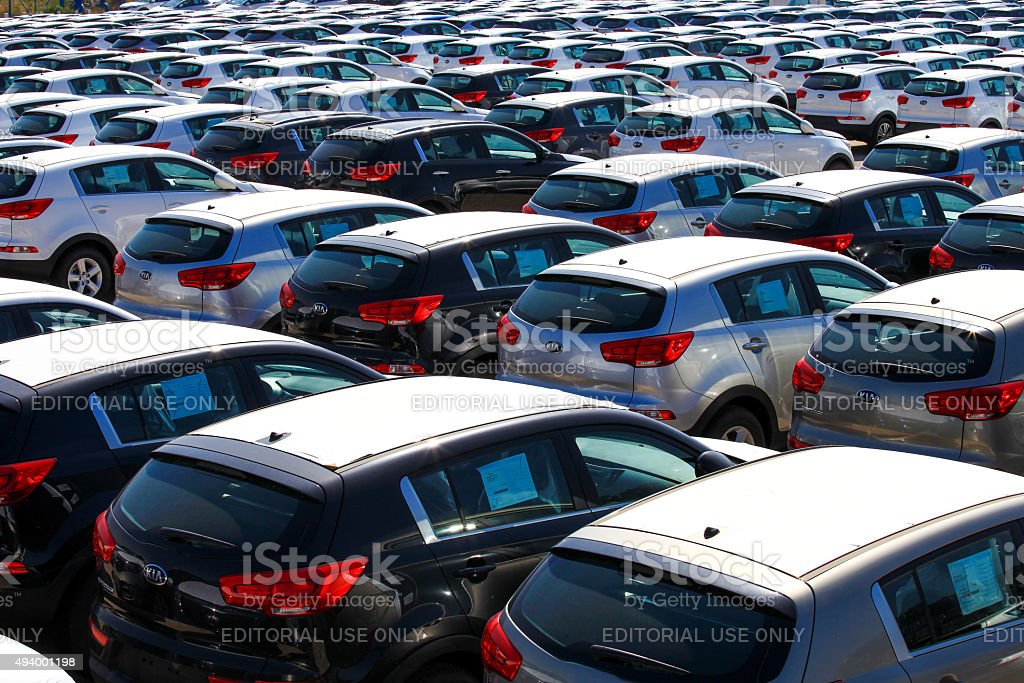 Rows of new cars covered in protective white sheet stock photo